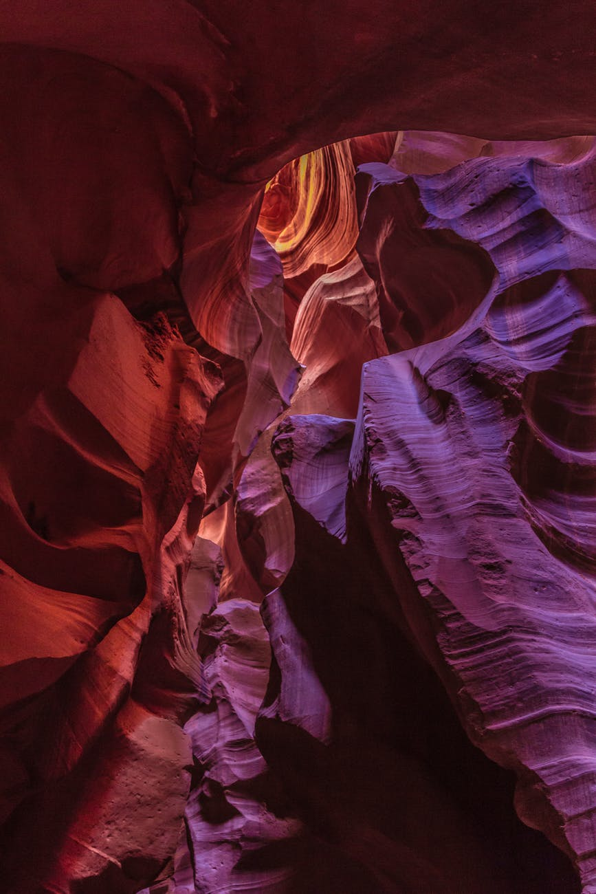 A carved rugged cave whose walls ae red and purple. Light enters it from above, The cave represents the carved heart of Jesus