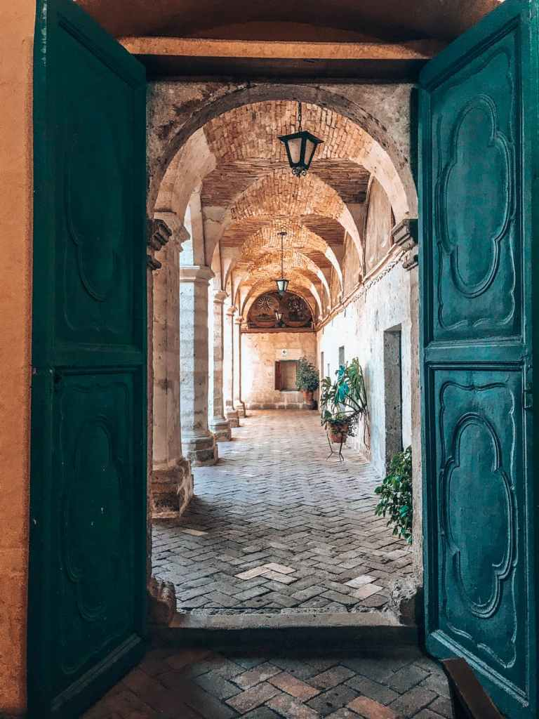 Green doors open onto a hall with open columns to the outside on one side and a closed wall with doors on the other side. This i