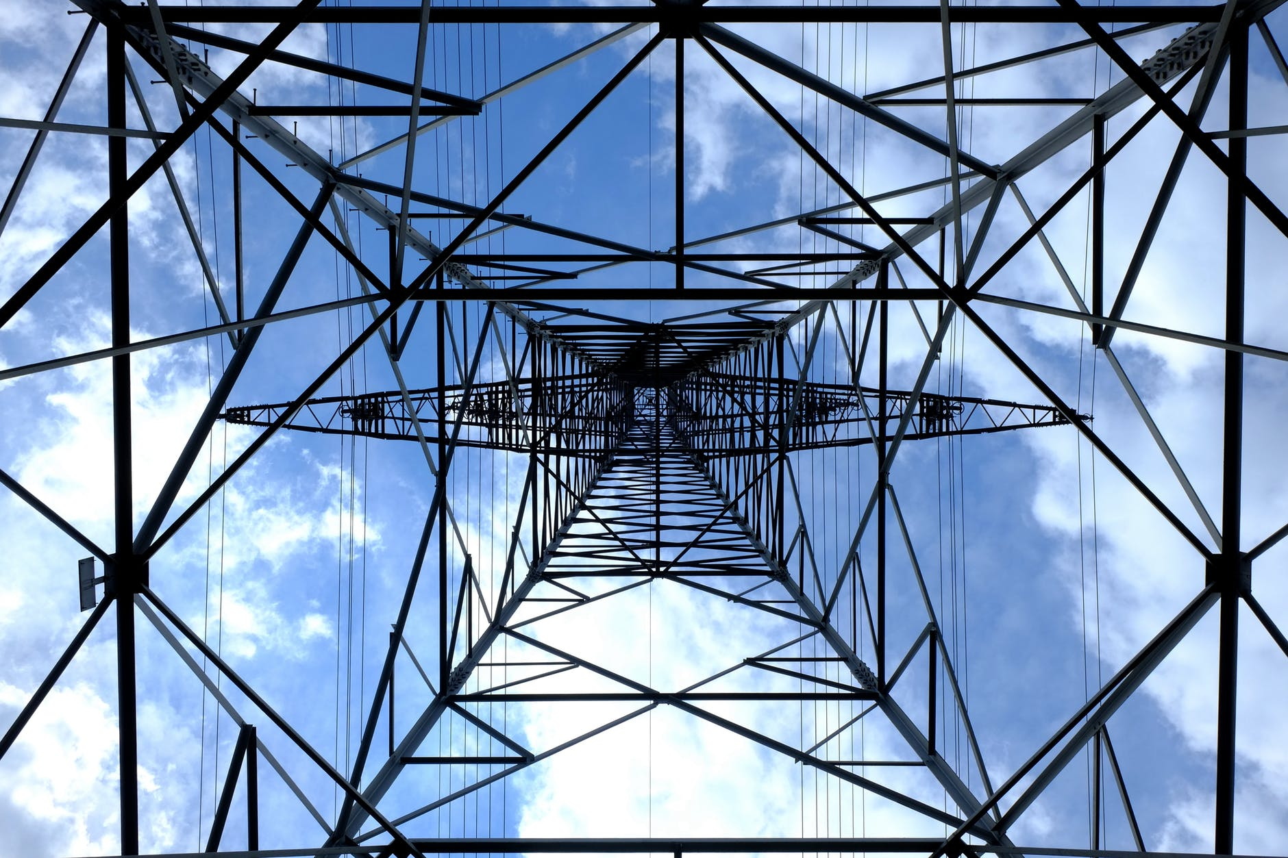 a power grid reaches straight up to a blue sky. Demand for power is high how do we meet our own demand for power?